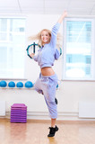 Smiling woman do stretching exercise in sports club