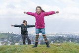 Two children fight the extreme wind from a hilltop poster
