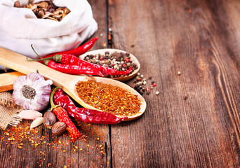 Red pepper and spices on wooden background