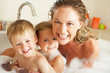 Mother With Children Relaxing In Bubble Filled Bath