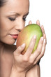 Closeup portrait of beautiful woman smelling fresh mango