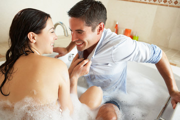 Woman Pulling Clothed Man Into Bubble Filled Bath