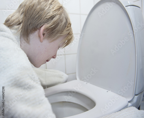 Young boy with stomach flu vomiting
