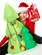 Women with santa hat presenting Christmas tree and a gift