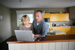 Couple using a laptop in the kitchen