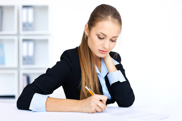 beautiful young business woman doing some paperwork in office