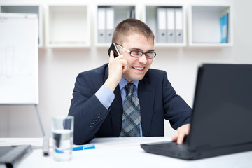 Portrait of smiling young business man talking on cell phone