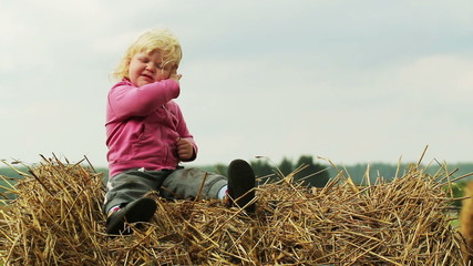child is sitting on a haystack