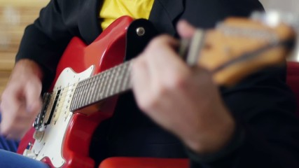 Male hands playing song  on red electric guitar