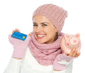 Smiling woman in knit winter clothing holding credit card