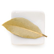 Bay Leaves in a white bowl on white background.