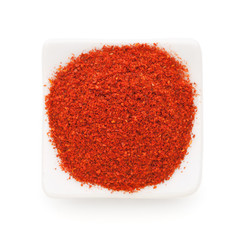 Paprika ground in a white bowl on white background.