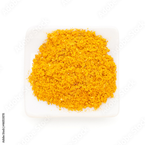 Curry ground (Madras Curry) in a white bowl on white background.