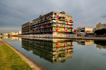 Immeuble recouvert de graffitis au bord du canal.