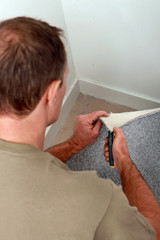 Man cutting carpet to fit a corner