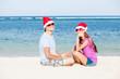 beautiful couple in santa hats on tropical beach of Bali