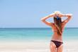 beautiful woman in a bikini on the beach looking on the horizon