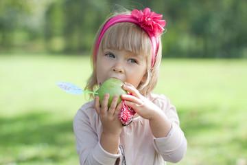 Красивая маленькая девочка с цветком в волосах ест яблоко