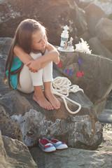 Красивая девушка, сидя на скале на берегу моря.