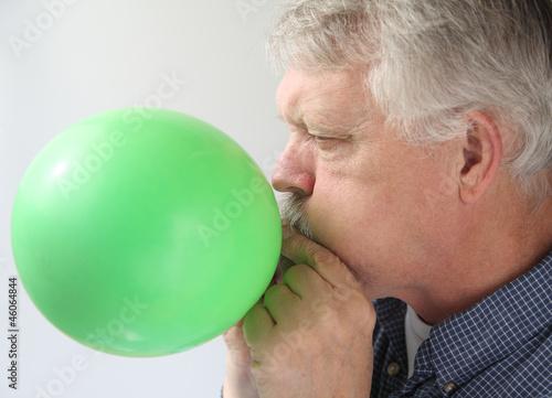 senior man blowing up balloon