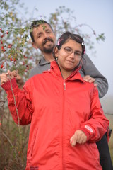 young couple picking rose hip