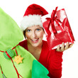 Women with santa hat presenting a red Christmas gift