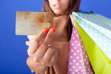 Beautiful shopping woman holding a credit card on blue backgroun