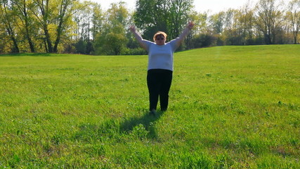 sport - overweight woman exercising on green meadow