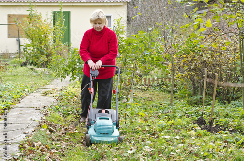 Woman mows grass lawnmower