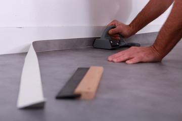 Man trimming linoleum against a skirting board