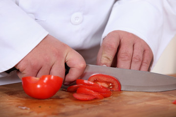 A cook slicing a tomato