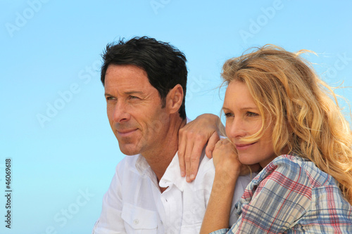 Headshot of couple with blue cloudless sky