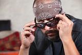 Intimidating male biker in bandana looking over his sunglasses