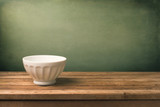 Grunge background with white bowl on wooden table