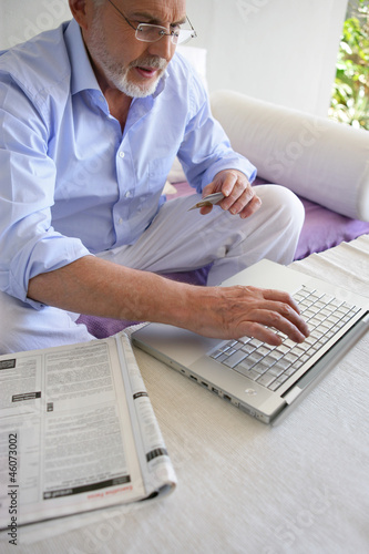 Gray-haired man shopping on-line