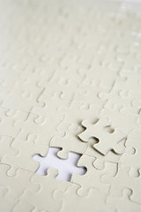 Blank jigsaw puzzle with one piece missing, close up