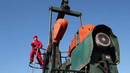 Worker Standing at Oil Pump Jack