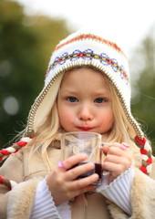 kleines Mädchen trinkt Kinderpunsch