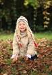 kleines Mädchen spielt im Herbstlaub
