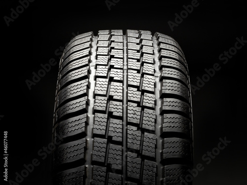 Winter tire on black background