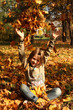 Girl playing with autumn leaves outdoors