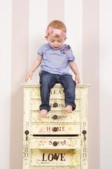 staunendes kind auf kommode mit offener schublade