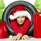 Miss santa watching through a snow tire with presents