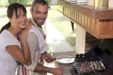Couple cooking food on outdoor barbecue