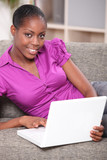 black woman doing computer and relaxing on a sofa