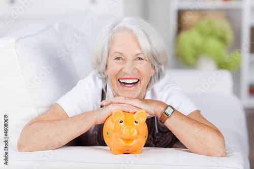 Leinwandbild Motiv lachende seniorin mit ihrem sparschwein