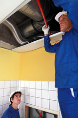 Two labourers checking ventilation system