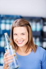 lächelnde frau mit einer flasche wasser im getränkemarkt