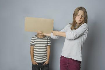 Mädchen hält Bruder ein Schild vor den Kopf
