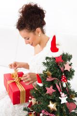 Frau packt Weihnachtsgeschenke aus